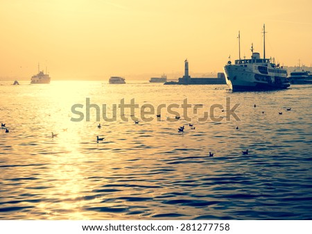 Sea voyage on a motorboat in Istanbul. Silhouettes of turkish steamboat in Istanbul with seagulls at sunset. Vintage passenger ship with soft light effect - travel concept in retro style. - stock photo