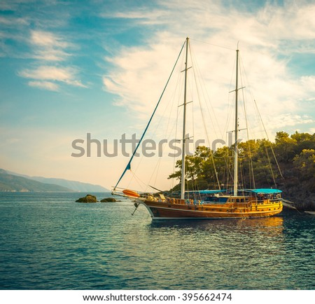 Sea voyage on classic yacht - luxury lifestyle in summer. Picturesque seashore with sailing vessel near island. Nautical landscape with wooden sailboat in retro style. - stock photo