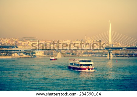 Sea voyage on the tourist motorboat, seaside view of Istanbul. Turkish steamboat in Golden Horn at sunset. Two passenger ships and New Bridge - travel in Turkey. - stock photo