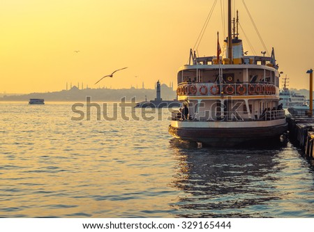 Sea voyage to Bosporus channel on the ferryboat of Istanbul. Turkish steamboat with seagulls at sunset. Vintage passenger ship in bright colors. - stock photo