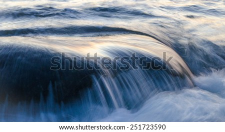 Sea water flowing over rock - stock photo