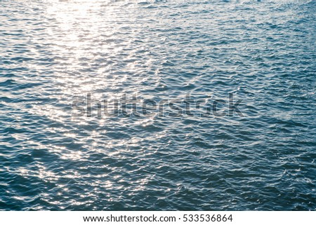 Sea water surface close up with sparkling sun light in evening