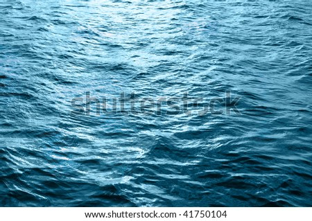 Sea water surface with ripple and cloud reflections - stock photo