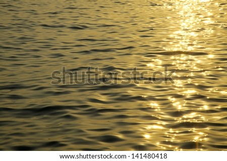 Sea water surface with sunset reflection - stock photo