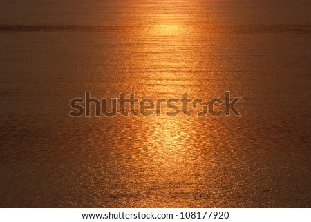 Sea water turns into golden by the reflection of sunset