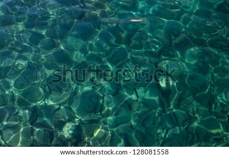 sea water with sunlight on turquoise pebbles background - stock photo