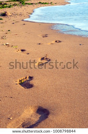 sea wave and footprints on the sand beach. Background summer vacation
