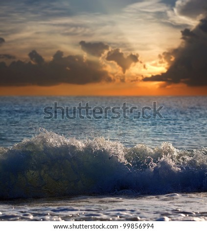 Sea wave during storm in sunset time - stock photo