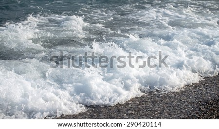 Sea wave foam on the pebble beach. - stock photo