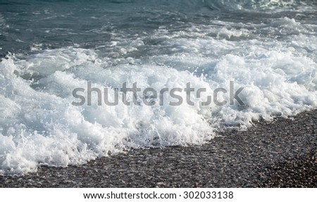 Sea wave foam on the pebble beach.