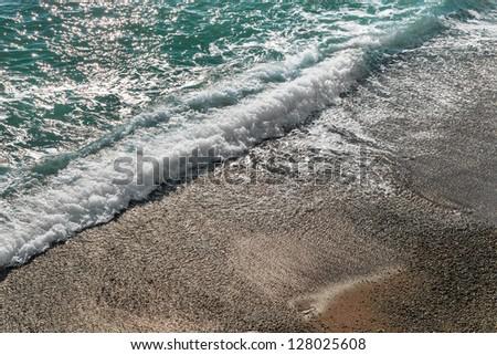 Sea wave incident on a pebble beach - stock photo