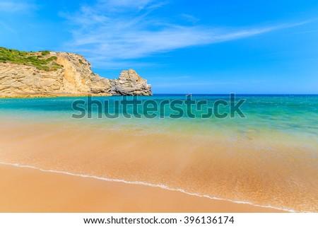 Sea wave on golden sand Barranco beach on western coast of Portugal - stock photo