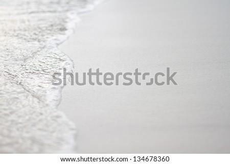 Sea wave on white sand. - stock photo