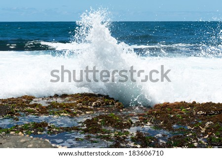 Sea wave slamming on the rocks of the coastline - stock photo