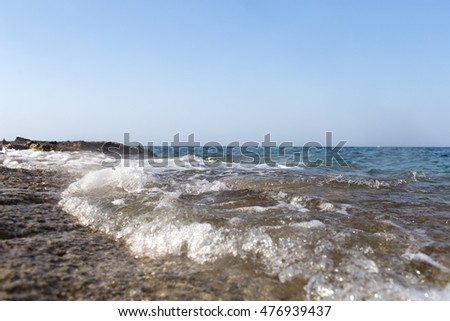 Sea wave splashing over the shore rocks with a high sea spray