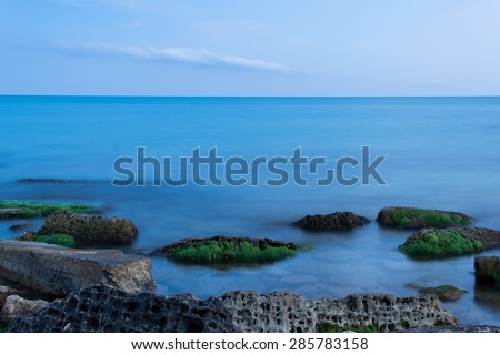 Sea waves and stones, long exposure used. Focus on the stones, evening time shoot. Great nature background. Relaxing and romantic seascape. - stock photo