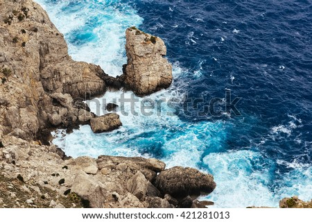 Sea waves breaking on a rocks in Majorca. Deep blue sea waves hit cliff. Sea waves hit rocks cliff. Mighty sea waves breaking on a cliff. Waves splashing over rocks. Strong ocean waves hitting rocks