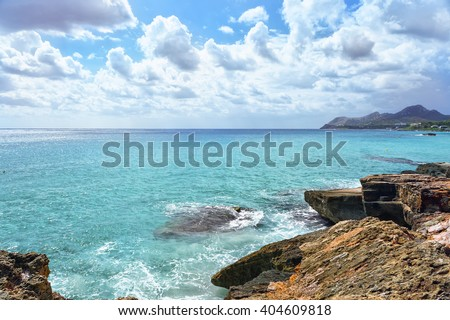 Sea waves crashing over rocks on wild stone beach in Majorca, Spain. Turquoise sea water, Majorca. Sea foam and brown rocks. Transparent sea.  Sunny day sea background. Sea waves beating against rocks - stock photo