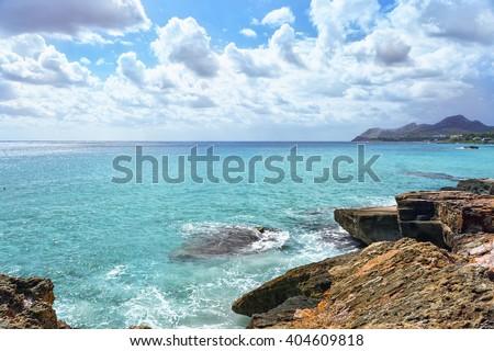 Sea waves crashing over rocks on wild stone beach in Majorca, Spain. Turquoise sea water, Majorca. Sea foam and brown rocks. Transparent sea.  Sunny day sea background. Sea waves beating against rocks - stock photo