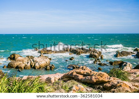 Sea waves crashing over rocks on wild stone beach in Phan Thiet area, Vietnam. Turquoise water, white sea foam and brown and yellow rocks - stock photo