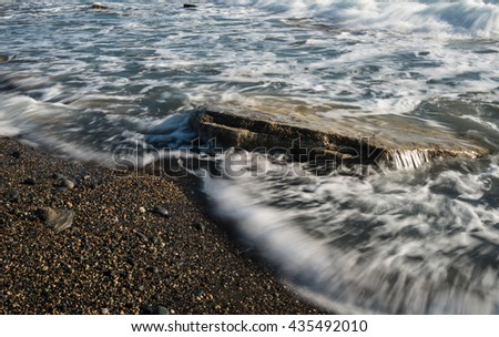 Sea waves flowing above a sea rock creating a beautiful nature water background. Long exposure photo. - stock photo