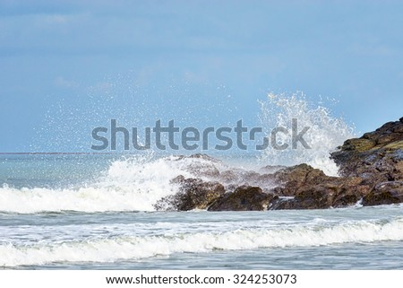 Sea waves impact rock on the beach