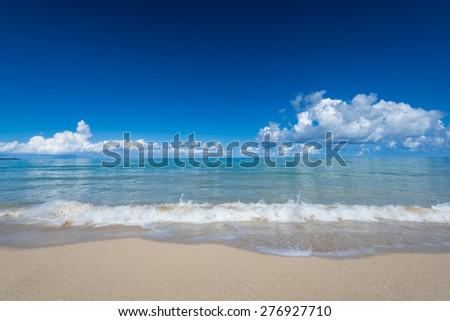 sea waves lash line impact on the sand beach under blue sky, phangnga, thailand - stock photo
