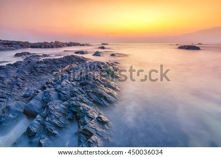 Sea waves lash line impact rock on the beach - stock photo
