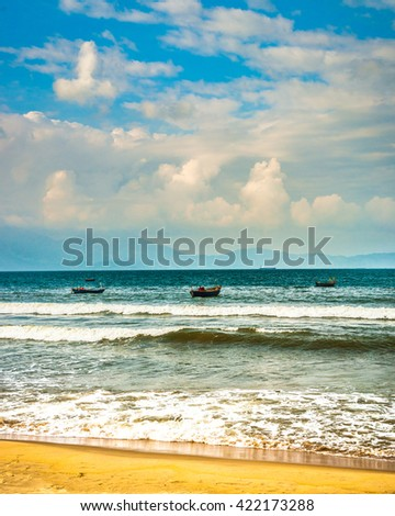 Sea waves near beach in Da Nang city, Vietnam. Traditional fishing boats are in the distance. Beautiful image of vietnamese nature. - stock photo