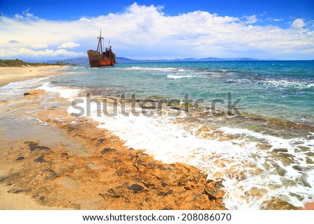 Sea waves on Selinitsa beach and rusty shipwreck in the background, Gythio, Greece