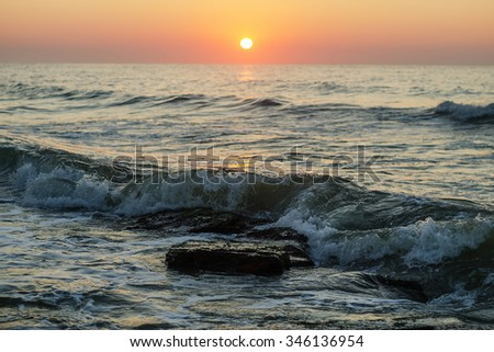Sea waves on the sunset. - stock photo