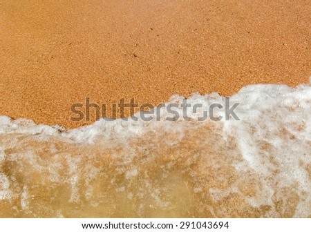 Sea waves roll on yellow fine sand while on vacation
