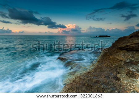 Sea waves with sunset and cloudy sky