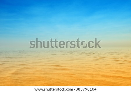 Sea with calm waters at sunset in summer - stock photo