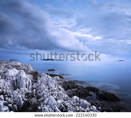 Sea with Rocky Shore at Evening. Smooth Water and Clouds. Long Exposure. Toned Photo. Copy Space. - stock photo