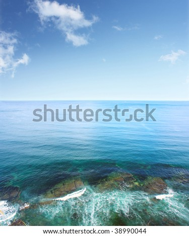 Sea with surf waves and blue sky with rare clouds - stock photo