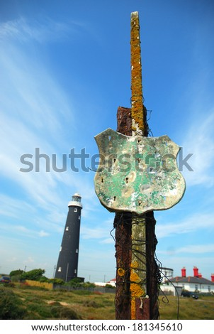 Sea worn post with lighthouse in background. - stock photo