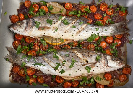 Seabass fish baked with vegetables, herbs and lemon - stock photo