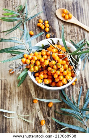 Seabuckthorn Berries in a Bowl with Leaves on Wooden Background - stock photo