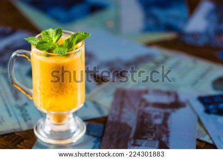 seabuckthorn tea in a glass cup decorated with mint leaves