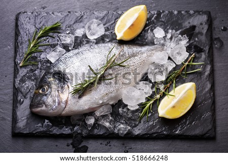 Seafood cooking preparation.Top view of dorado and shrimps with herbs and lemon on black slate.