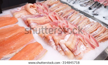 Seafood counter display of fish. White cod and tilapia fillets with orange salmon fillets - stock photo