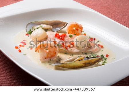 Seafood cream soup with shrimps on a white plate