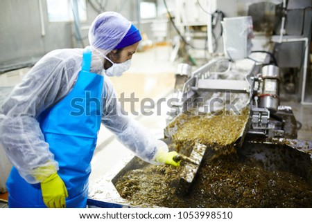 Seafood factory staff standing by production line and mixing seaweed salad in huge container with special handtool
