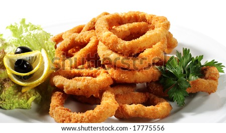 Seafood - Fried Calamari. Deep-fried Squid Dressed with Salad Leaves, Parsley, Olives and Lemon. Isolated on White Background - stock photo