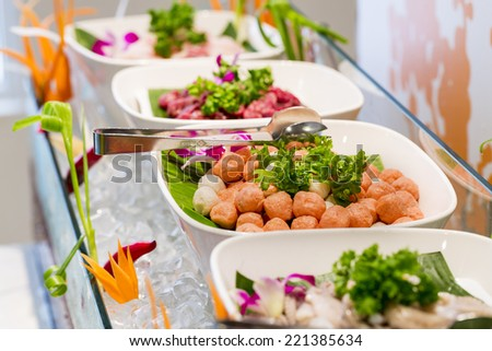 Seafood, Meat, Fish on bowl. Typical hot pot dishes include thinly sliced meat, leaf vegetables, mushrooms, wontons, and seafood. Vegetables - stock photo