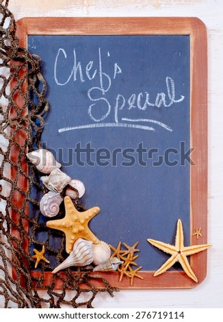 Seafood menu image of blackboard with fishnet and seashells and starfish gathered on left. The slate on the blackboard is rough and the brown frame is worn. Message is chef's special with copy space - stock photo