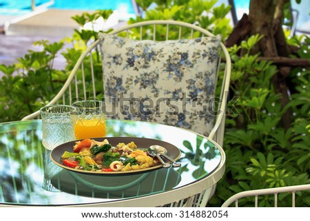seafood noodle on plate and orange juice water in garden