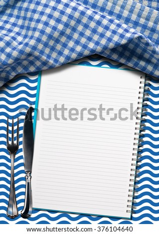 Seafood - Notebook with Blue Waves / Open notebook for recipes or fish menu on a background with blue and white waves, silver cutlery and blue and white checkered tablecloth - stock photo