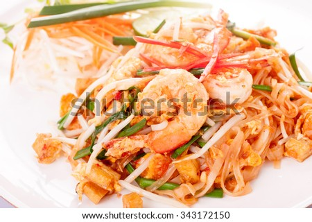 Seafood pad Thai dish of fried rice noodles on a square white plate with chopsticks and grated carrot garnish. - stock photo